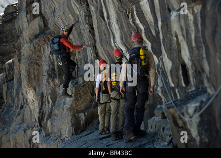 A group of climbers ascend a rock pitch in the Canadian Rockies, British Columbia, Canada. - Stock Photo