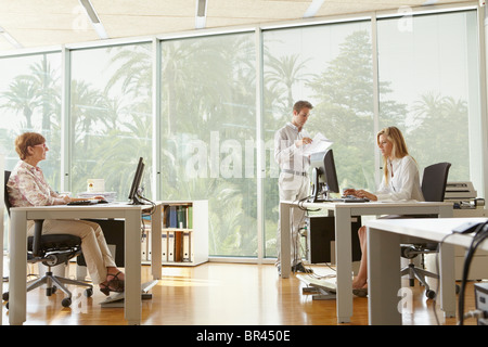 Young man in office with colleagues - Stock Photo