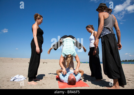 People practicing acroyoga on the beach Blijburg in Amsterdam, the Netherlands. Acroyoga is a special, acrobatic - Stock Photo