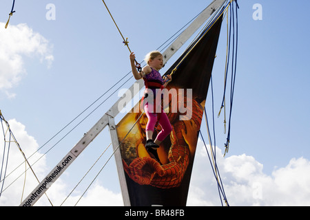 A Little Girl on a Catapult Bungee ride at a fairground - Stock Photo