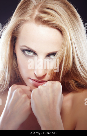 Beautiful lady with clinched fists protecting herself as a symbol of woman's right - Stock Photo