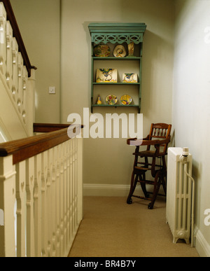 Small green shelves on wall of traditional cream landing with child's antique highchair in corner - Stock Photo