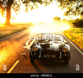 A sports car being driven along a country road on a summers evening - Stock Photo