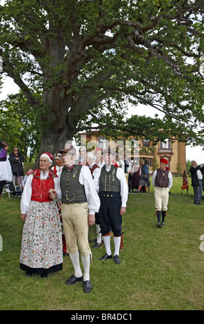 People in traditional Swedish folk costumes at midsummer celebration. Naas castle estate, Sweden. - Stock Photo