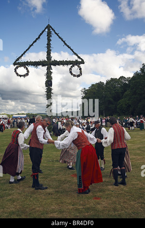 People in folk dress costumes dance around may pole. - Stock Photo