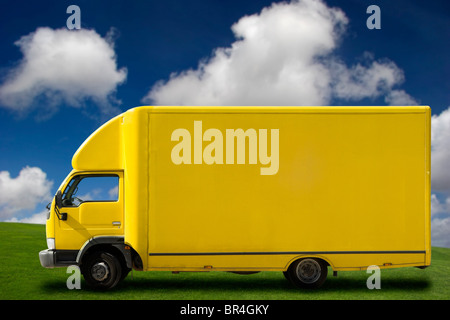 Yellow truck on a beautiful green meadow with copy space for text - Stock Photo