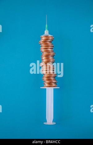stacked coins make medical syringe barrel
