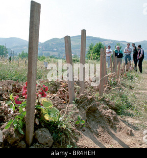 Aid workers view mass Graves in Kosovo. - Stock Photo