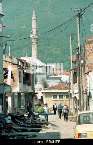 People walk the street past the destruction in Peja, Kosovo. - Stock Photo
