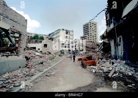 Children run through the NATO bomb damage in Pristina Kosovo. - Stock Photo