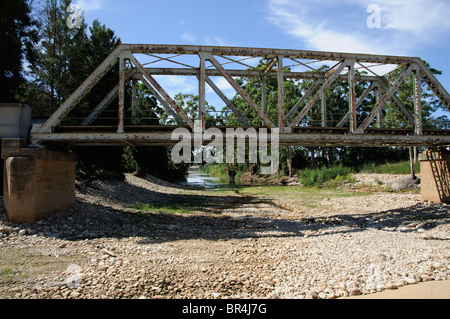 Steel railway bridge passing over the part dried riverbed of the Buffeljags River in the Cape Overberg close to - Stock Photo