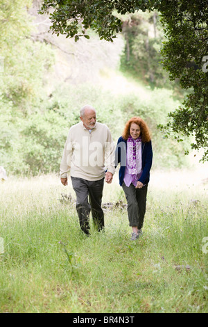 Caucasian couple walking in woods - Stock Photo
