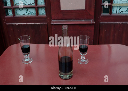 Carafe of wine and two glasses in front of l'Auberge Ravoux, Auvers-sur-Oise, France - Stock Photo