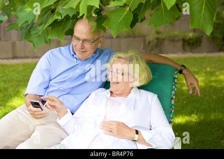 Happy senior couple smartphone in garden - Stock Photo