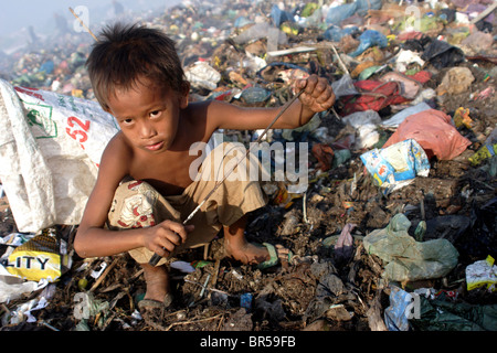 A young child worker grasps the gaff he is using to collect plastic at The Stung Meanchey Landfill in Phnom Penh, - Stock Photo