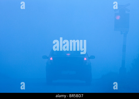car waiting at rural railroad crossing with red lights blinking in fog - Stock Photo