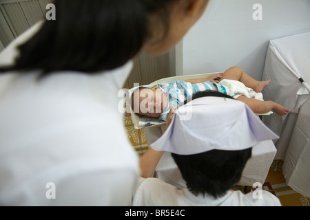 Nurse weighing baby in doctorís office - Stock Photo