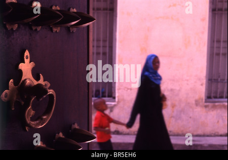 Young Zanzibari woman and child and beautiful wooden door. Stone Town. Zanzibar. - Stock Photo