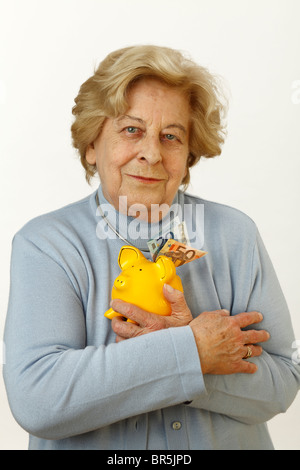 Old woman, 80 years old, holding a piggy bank - Stock Photo