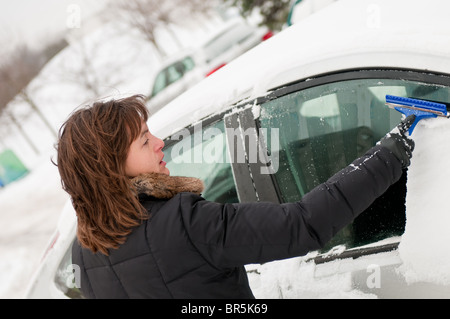 Young woman cleaning car windows from snow in winter season - Stock Photo