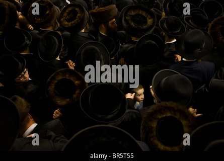A young Orthodox Jewish boy surrounded by hundreds of Orthodox Jewish men wearing black coats and hats. - Stock Photo