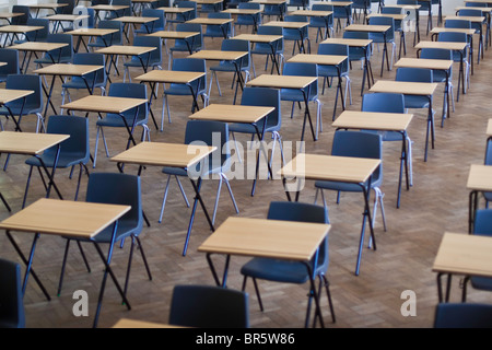 Desks and chairs set out for exams in a school hall in the United Kingdom. - Stock Photo