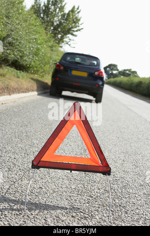 Car Broken Down On Country Road With Hazard Warning Sign In Foreground - Stock Photo