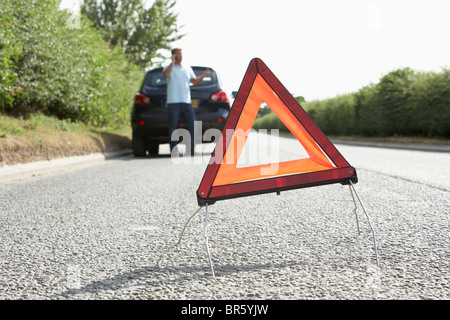 Driver Broken Down On Country Road With Hazard Warning Sign In Foreground - Stock Photo