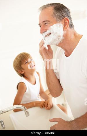 Grandson Watching Grandfather Shaving In Bathroom Mirror - Stock Photo