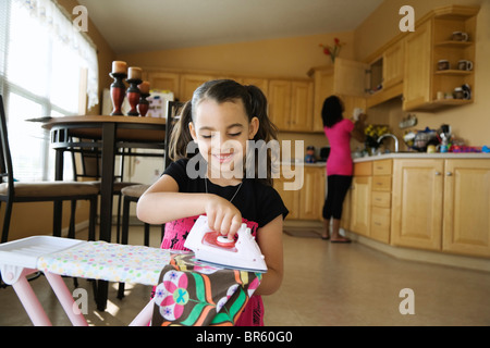 Girl using toy iron and ironing board in kitchen - Stock Photo