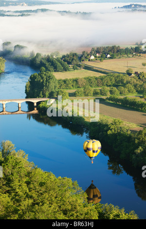 Hot air balloon and morning mist over the river Dordogne; France - Stock Photo