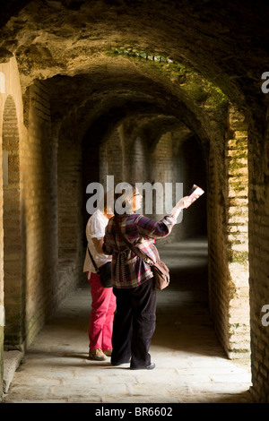 Two women tourists in hallway that circles the amphitheatre at the ruined Roman city of Italica / Itálica near Seville, - Stock Photo