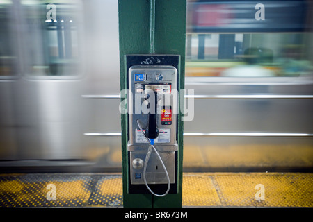 A coin operated public pay telephone on the Sheridan Square subway station platform in New York - Stock Photo