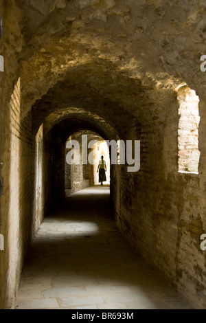 Distant tourist in hallway that circles the amphitheatre at the ruined Roman city of Italica / Itálica near Seville, - Stock Photo
