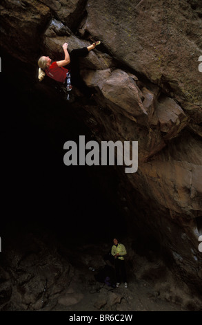 A young woman climber lead climbing on an overhanging rock climbing route. - Stock Photo