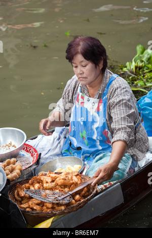 Cooking fast food. Woman food seller in Long Tailed Boat, Bangkok   The Damnoen Saduak Floating Market,  vendors - Stock Photo