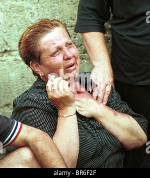 Women react to their homes burning down in fires in Prizren, Kosovo. - Stock Photo