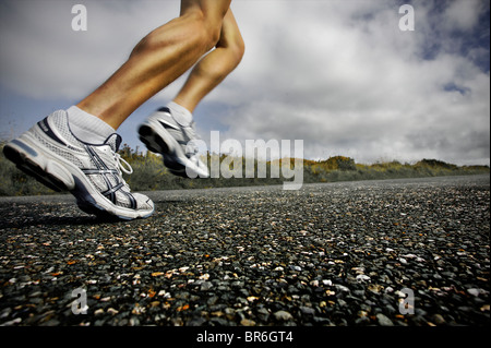 A close, low angle view of a male athlete running along a tarmac road with his large leg muscles showing - Stock Photo