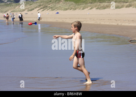 Boy standing in shallow water and throwing a nerf ball on a beach in Woolacombe North Devon UK - Stock Photo