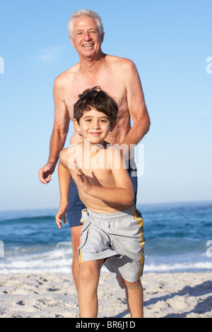 Grandfather, Father and Grandson Running Along Beach - Stock Photo
