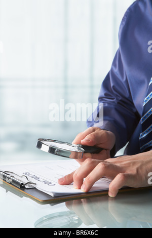 Businessman examining contract in the office using magnifying glass - Stock Photo