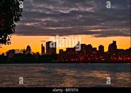Looking over the River Thames towards Wapping and the City, at sunset with low passing clouds, London, England, - Stock Photo