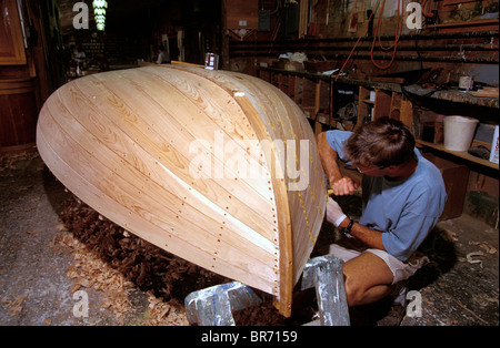 A traditional Beetlecat builder working on the bottom of a new boat at the International Yacht Restoration School - Stock Photo