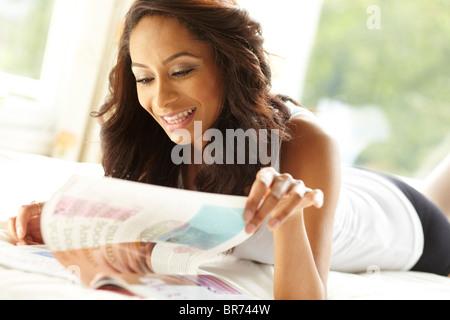Ethnic girl reading magazine - Stock Photo