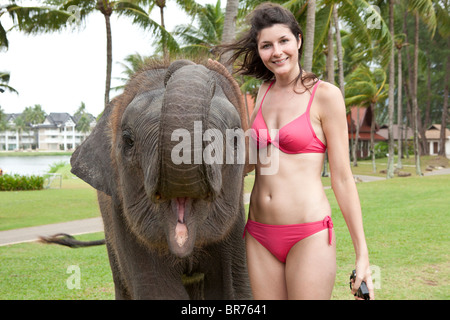 Tourist posing with an elephant at a holiday resort in Thailand - Stock Photo