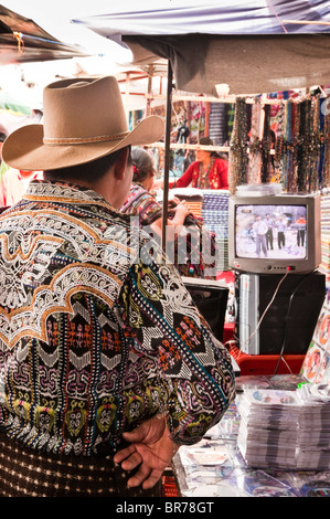 Mayan man looking a TV show on a small musical business stand in the Solola Market, Solola, Guatemala. - Stock Photo