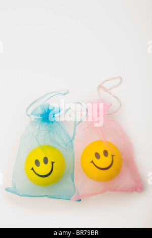 Yellow Happy Faces In Blue And Pink Bags; Edmonton, Alberta, Canada - Stock Photo