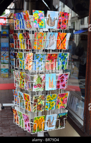 Colourful postcards on sale in a rack outside a shop - Stock Photo
