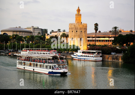 A river cruiser taking passengers past the Torre Del Oro  on Seville's Guadalquivir river at twilight. - Stock Photo