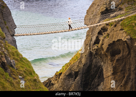 Young woman crossing the Carrick-a-Rede rope bridge near the village of Ballintoy on the County Antrim coast, Northern - Stock Photo